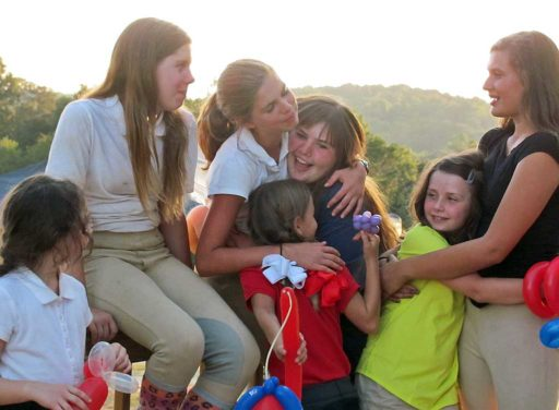 group of riding students hugging each other