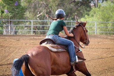 Western rider with helmet practicing barrel racing pattern