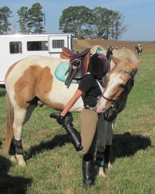 rider stretching leg before xcountry ride with helpful horse watching her