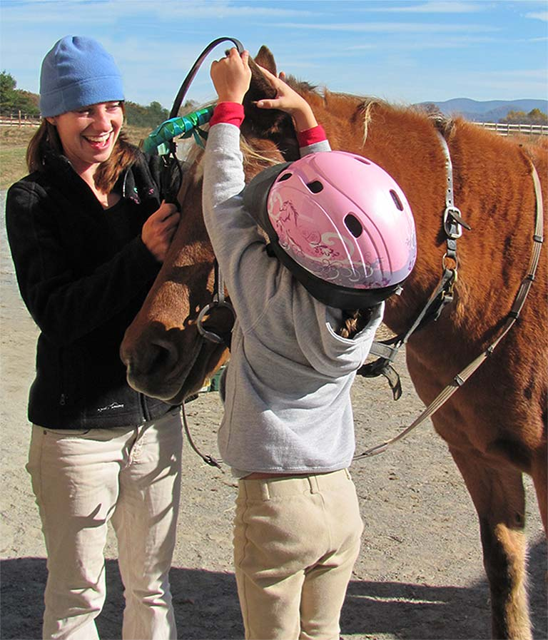 riding instructor helps young student put bridle on pony