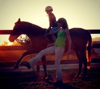 riding instructor teaching lesson to student on pony as sun sets