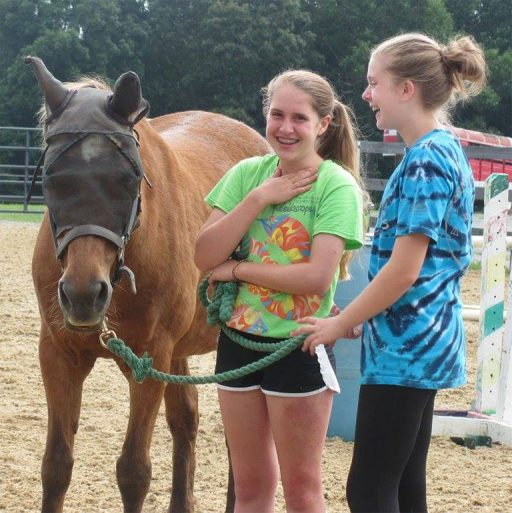 two students laughing while attempting groundwork with pony